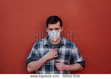 A Guy In A Checked Shirt And Mask On A Red Background Looks At The Camera.