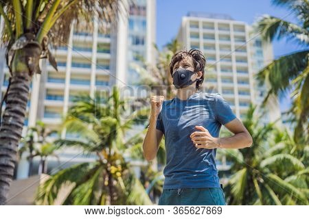 Man Runner Wearing Medical Mask. Running In The City Against The Backdrop Of The City. Coronavirus P