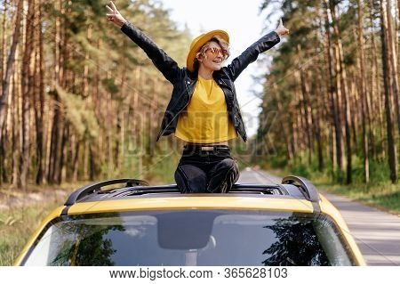 Happy Woman Sitting On Car Sunroof Freedom Concept. Road Trip Joy. Hipster Beautiful Caucasian Girl