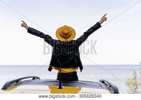 Hipster Girl Sitting On Yellow Car Roof Back View. Woman With Raised Arms At Ocean Summer Freedom Co