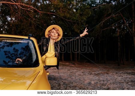 Caucasian Funny Woman Leaning Out Of Car Window. Beautiful Girl Have Fun, Express Emotion On Road Tr