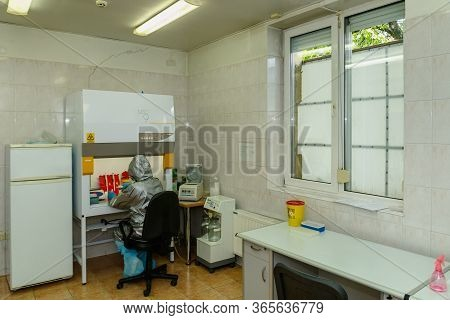 Uzhgorod, Ukraine - May 8, 2020: Epidemiologist In Protective Suit, Mask And Glasses Diagnoses Covid