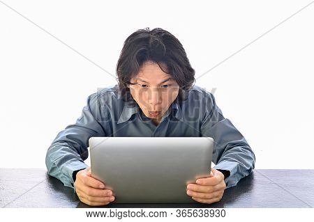 Asian Business Man Looks Very Surprised At His Laptop , Sitting Looking At Some Unbelievable News At