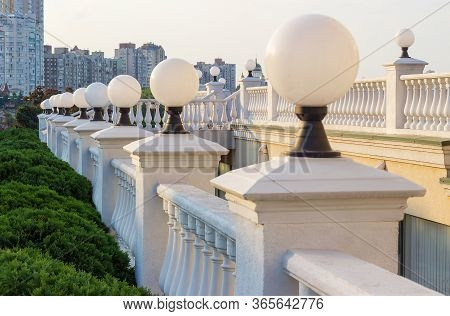 White Stone Balustrades With Shaped Balusters And Spherical Streetlights On Open Area Against The Mu