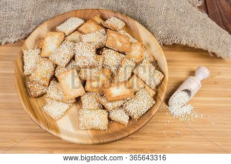 Flat Rectangular Flaky Crispy Cookies With Candied Roasted Sesame On The Wooden Dish And Sesame Seed