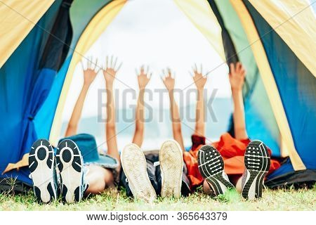A Group Of Happy Friends Sleep And Raised Their Hands In A Tent While Camping Travel During The Holi