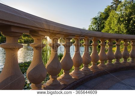 Fragment Of Stone Balustrade With Shaped Balusters Over The Decorative Pond In Summer Park At Sunset