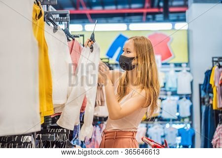 Woman In A Clothing Store In A Medical Mask Because Of A Coronovirus. Quarantine Is Over, Now You Ca