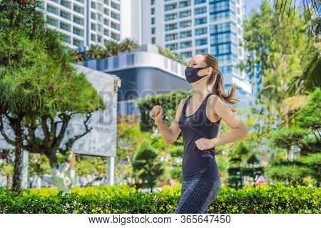 Woman Runner Wearing Medical Mask. Running In The City Against The Backdrop Of The City. Coronavirus
