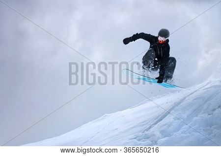 A Professional Snowboarder Girl In Flight After Jumping From A Snow Eaves Makes A Rake Against The G