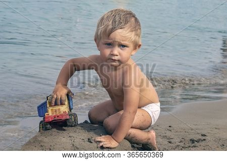 A Little Boy Plays On The Beach With A Toy Truck. Potter Of A Beautiful Child 2 Years Old. Serious F