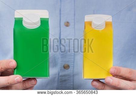 Green And Yellow Cartones Milk Or Juice In Mens Hands. Copy Space, Mock Up.