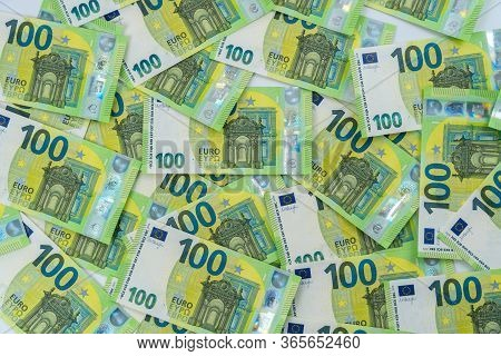 Banknote Of 100 Hundred Euros Are Scattered In A Chaotic Manner. European Currency Lies On The Table