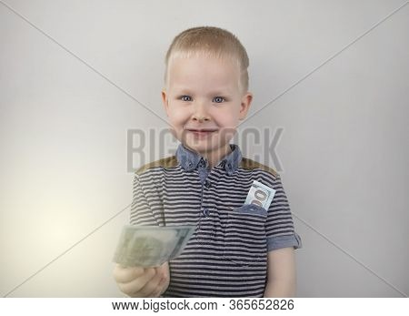 A Blond Boy Holds Dollars In His Hands. The Child Rejoices In The Appearance Of Pocket Money. Financ