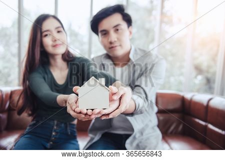 Couple Hands Holding Housing Model For Future Real Estate Saving, Attractive Asian Couple Hand Joint