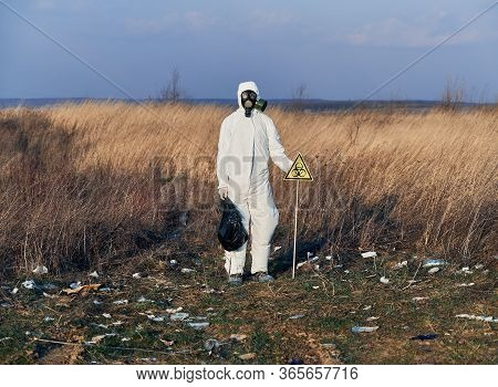 Environmentalist Wearing White Protective Suit, Gas Mask, Standing In The Field Full Of Garbage, Nex