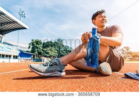 Sport Man Sitting And Holding Water Bottle On Track Race At Sport Stadium In The Morning.