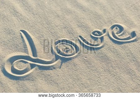 Wedding White Gold Ring And Word Love In The Sand.