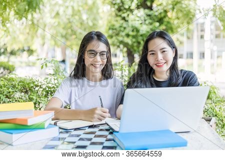 University Students Use Laptop For Reading And Learning Concept;