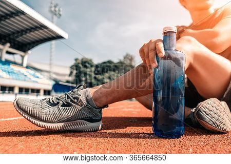 Sport Man Sitting And Holding Water Bottle  On Track Race At Sport Stadium In The Morning. Sport, Wo