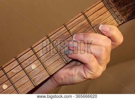 A Woman's Hand With A Manicure Holds A Chord On A Guitar. The Girl Plays The Guitar. Fingerboard And