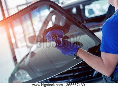 Automobile Special Workers Replacing Windscreen Of A Car In Auto Service