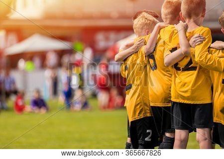 Kids Sport Team In Yellow Golden Jerseys Having Pep Talk With Coach. Children Soccer Team Motivated