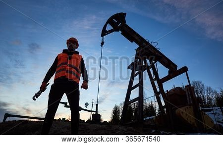 Male Oil Worker Standing Near Petroleum Pump Jack. Petroleum Engineer In Work Vest And Helmet Holdin