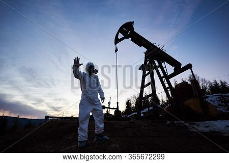 Silhouette Of Male Scientist Showing Stop Sign While Standing On Territory Of Oil Field With Pump Ja