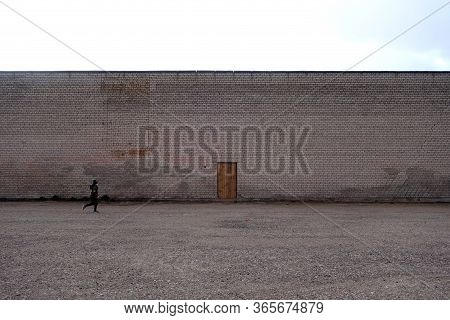 Boy Running In Front Of Wooden Door On Brick Wall. Conceptual Background
