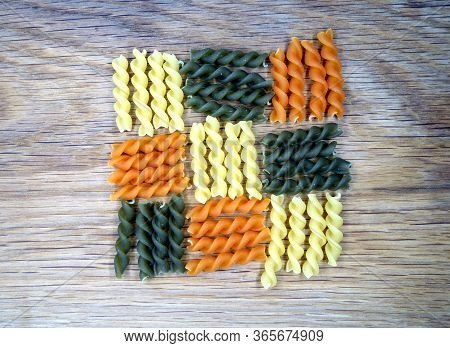 Dry Multi-colored Pasta On Wooden Board. Food And Ingredientes Background.