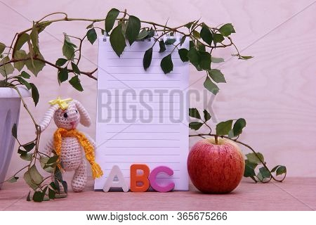 Abc - The Letters Of The English Alphabet Next To The Clean Page Of The Notebook. A Knitted Toy Hare