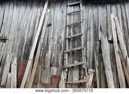 Old Weathered Wooden Ledder In Front Of Barn Almost Ruined. Background And Rural View