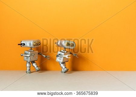Two Metal Silver Robots Are Walking. Simplified Symbolic Toy Robotic Characters On An Orange Backgro
