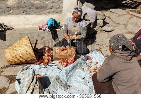 Kagbeni, Mustang District, Nepal - November 19, 2016: Nepalese Women Chopping Yak Meat On The Street