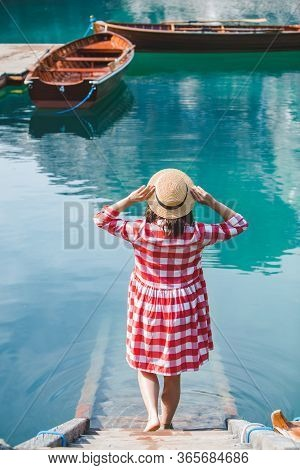 Young Woman In Red Sundress Walking By Stairs To Lake Water