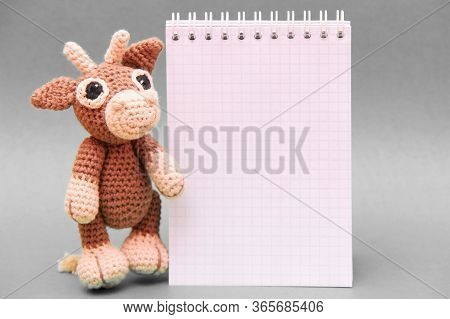 The Bull Is The Symbol Of The New Year 2021. A Knitted Brown Toy Bull Next To A Notepad . Copy Space