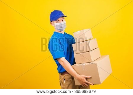 Asian Young Delivery Worker Man In Blue T-shirt And Cap Uniform Wearing Face Mask Protective Lifting