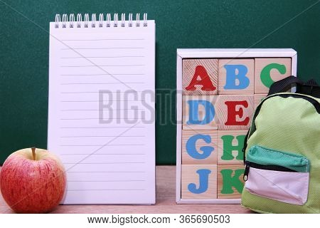 Wooden Blocks With Letters Of The English Alphabet , Notebook And The Apple Next To Them. Back To Sc