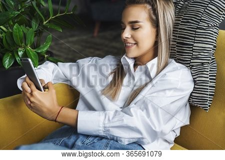 Female Relaxing At Home, Using Smartphone To Text Messages, Share Photos, Communicate With Friends,