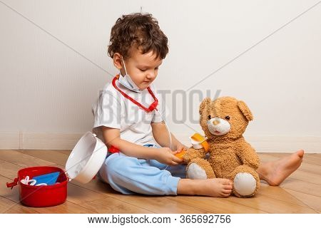Baby In A Medical Mask Plays With A Teddy Bear. Baby Boy In A Mask Puts On A Mask A Toy. Virus Prote