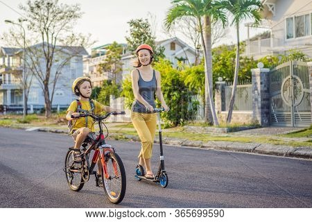 Active School Kid Boy And His Mom In Safety Helmet Riding A Bike With Backpack On Sunny Day. Happy C