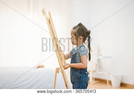 Little Girl Draws Chalk On Blackboard With Happiness At Home For Online Study Class. Online Learning