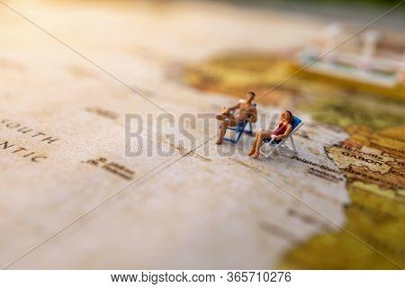 Miniature People Sit On Beach Sunbath Seats On Vintage World Map And Ship, Summer Concept.