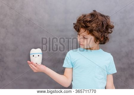 Cute Curly Boy Holds Big Tooth And Surprised On Gray Background. The Boy Lost The First Milk Tooth.