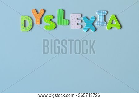Word Dyslexia Written Of Wooden Letters On Azure Background. Inscription Dyslexia Formed With Colorf