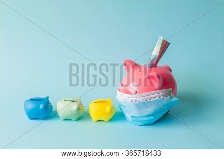 Piggy Bank, Wearing Protective Mask, With Euro Notes And Following Small Piggy Banks, On Isolated Ba