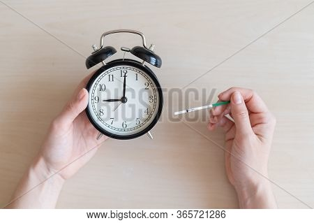 Woman Holds Negative Ovulation Test And Alarm Clock. Female Fertility Biological Clock Concept. Not