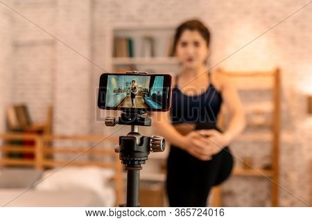 20s Young Asian Woman In Sportswear Doing Talking To Camera And Explaining Fitness Tutorials Online.