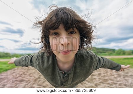 Joyful Boy In Flight (levitation Effect). Distortion Of An Ultra Wide Angle Lens.